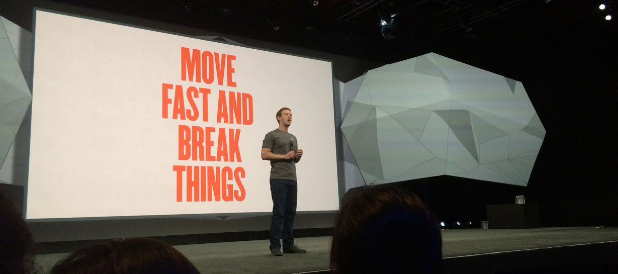 Mark Zuckerberg in front of a Move Fast poster